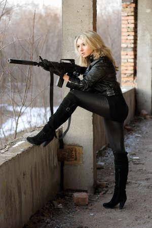 ljuddämparen: Blond flicka på höga klackar som tar ett skott med maskingevär