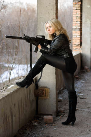Blond girl on high heels taking a shot with machine gun