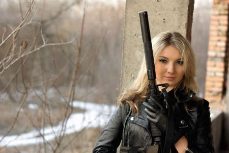 Beautiful girl with a big gun in front of the winter forest
