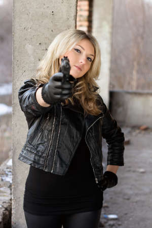 Arrogant young woman in leather jacket with a gun photo