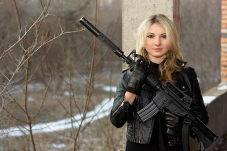 Scared girl in leather jacket with a big rifle photo