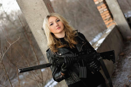 Beautiful young woman with a rifle  in neglected building photo
