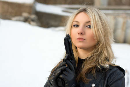 Hot girl holding a gun against the snow photo