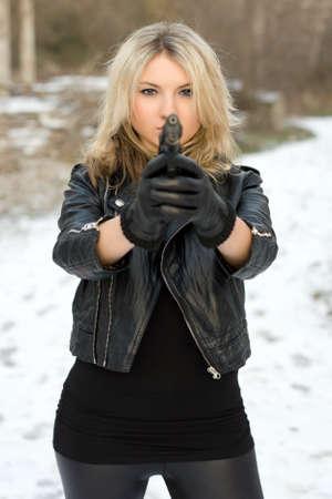 Seductive girl aiming with a gun against the snow photo