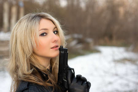 one armed: Hot girl holding a gun in winter forest Stock Photo