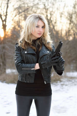 mujer con arma: Curioso mujer bonita con una pistola en el bosque de invierno