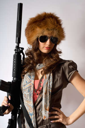 the silencer: Young stylish woman in hat with a gun Stock Photo
