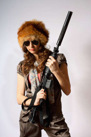 Beautiful girl in fur hat holding a rifle photo