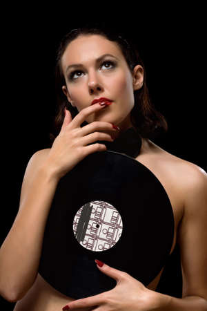 Portrait of a nice young brunette with vinyl photo