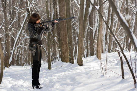 Armed woman in the forest target at victim photo