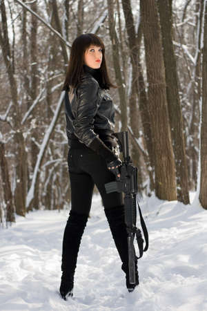 bata blanca: Joven y bella mujer con un rifle de los bosques en invierno