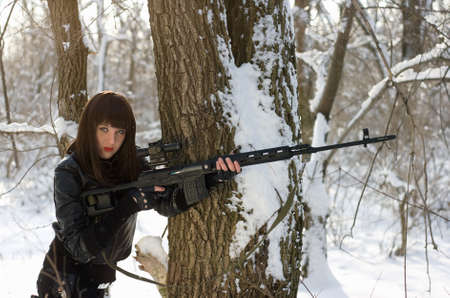 Gorgeous young woman with a sniper rifle near the tree photo
