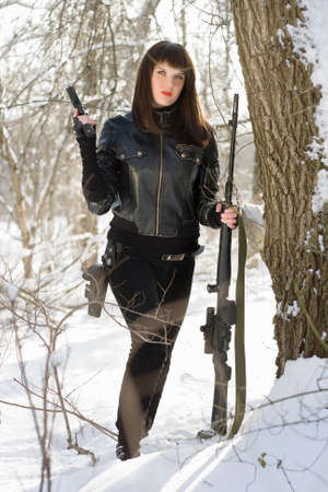 Armed beautiful young lady in a winter forest photo