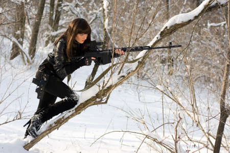 Gorgeous young woman with a sniper rifle in winter forest photo