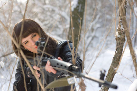 Portrait of girl with a sniper rifle in winter forest photo