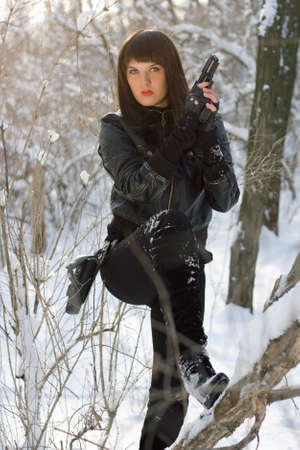 Sexy young woman with a pistol in winter forest