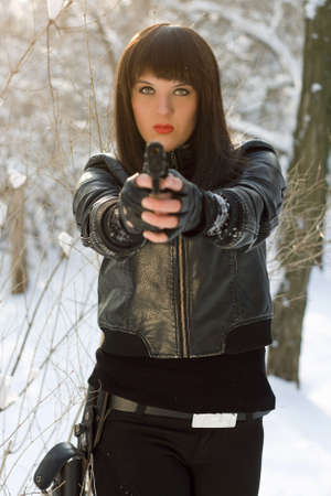 Portrait of sexy young woman with a pistol in winter forest Stock Photo