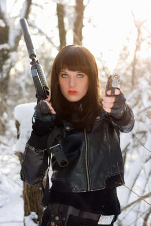 Portrait of armed beautiful young lady in winter forest photo