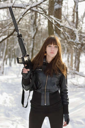 Young sexy brunette with the raised rifle photo