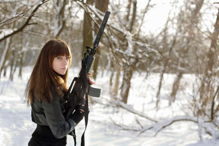 Armed brunette woman in the winter forest Stock Photo