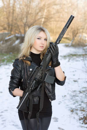 silencer: Portrait of sexy young blonde with a gun outdoors