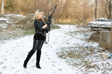 Beautiful young woman with a gun outdoors photo