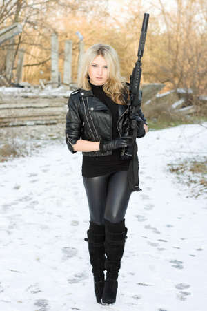 Young pretty woman with a gun outdoors Stock Photo - 12840370