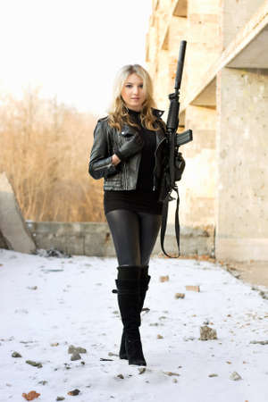 the silencer: Sexy smiling girl holding a weapon outdoors
