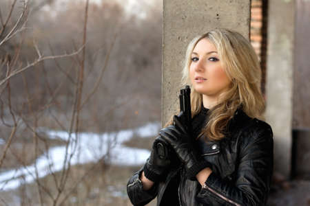 one armed: Cute girl in leather jacket holding a gun Stock Photo