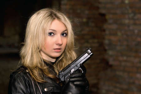 Scared beautiful woman with a gun in abandoned house Stock Photo