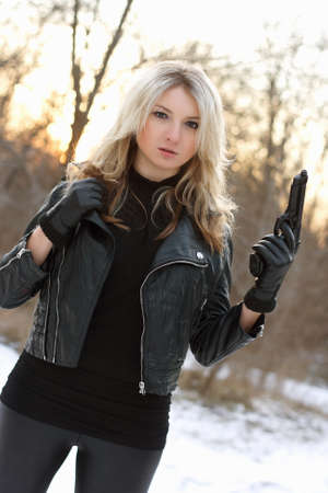 Serious armed woman shooting in winter forest photo