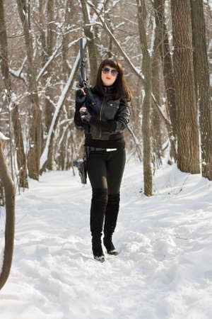 Woman in black with weapon on the snow