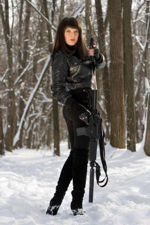 Pretty young woman with weapon in their hands photo