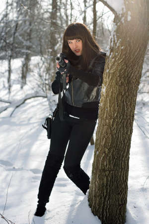 silencer: Gorgeous young woman with a rifle near the tree Stock Photo