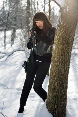 ljuddämparen: Underbara ung kvinna med ett gevär nära trädet Stockfoto