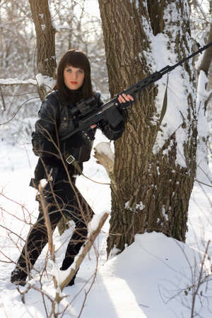 Young woman with a sniper rifle near the tree photo