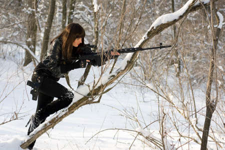 Young woman with a sniper rifle in winter forest photo