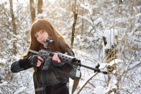 gun sight: Armed young brunette girl aiming a gun Stock Photo