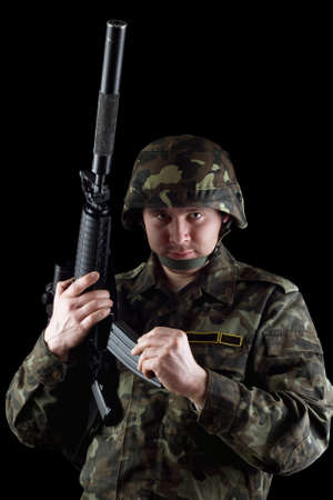 reloading: Soldier reloading magazine of m16 in studio. Isolated