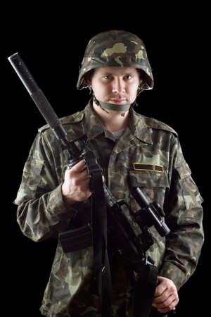 grasping: Armed soldier grasping m16 in studio. Isolated
