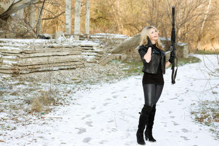 Attractive young woman with a gun outdoors photo