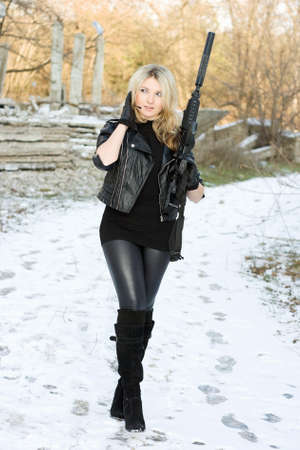 the silencer: Perfect young woman with a gun outdoors