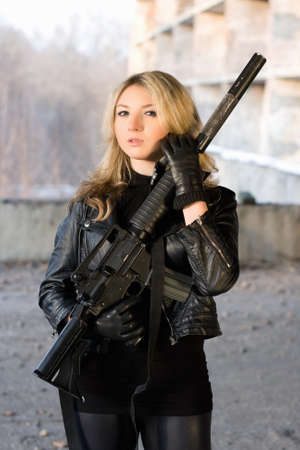 airsoft: Hot woman in leather jacket holding a rifle Stock Photo