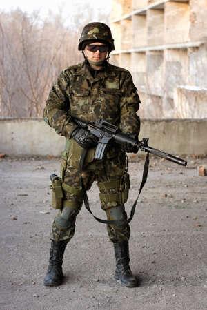 soldado: Hombre joven militar con un rifle de gran