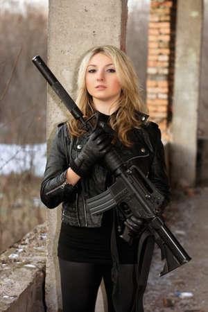 ljuddämparen: Underbara ung kvinna med ett gevär i försummade hus
