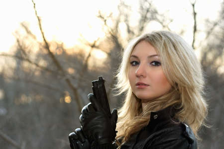 one armed: Blonde young woman with a gun at the sunset Stock Photo