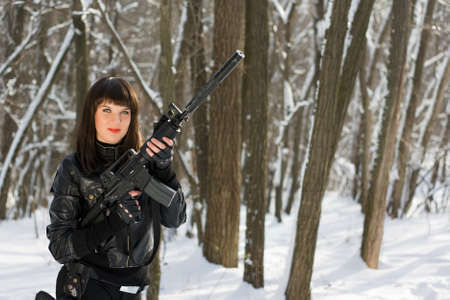 the silencer: Portrait of sexy young woman with a rifle in forest Stock Photo