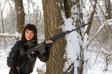 Pretty young woman with a sniper rifle near the tree photo