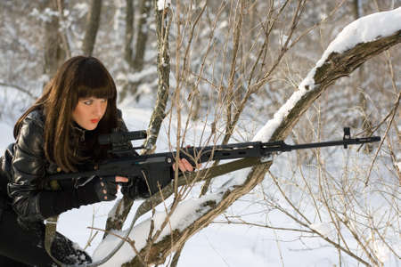 Portrait of young woman with a sniper rifle in winter forest photo