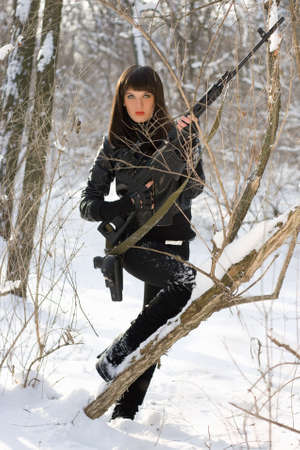 Attractive young woman with a sniper rifle in winter forest photo